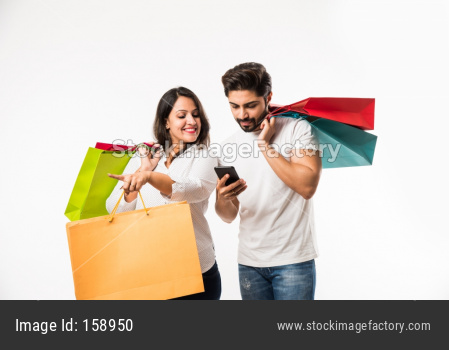 Indian young couple shopping bags and smart phone or mobile, clicking selfie or locating store, standing isolated over white bac