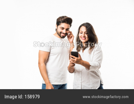 Indian couple using smartphone / mobile handset, standing isolated over white background