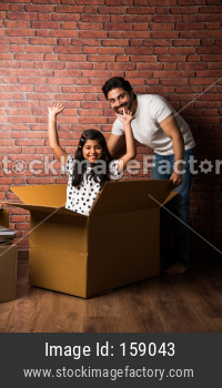 Small girl coming out of cardboard box and father looking at her happily