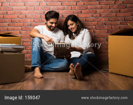 Indian couple relaxing while shifting/unpacking home, sitting between packaging boxes, looking at Photo frame, cel phone