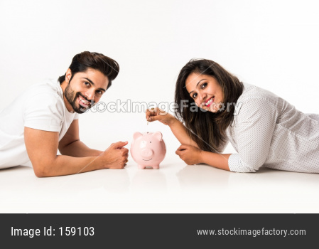 Indian couple with piggy bank, isolated over white background