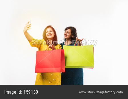 Indian Mother daughter sisters shopping with colourful bags, standing isolated over white background