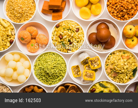 Rangoli of sweets and Farsan/snacks in bowls with diya over white background