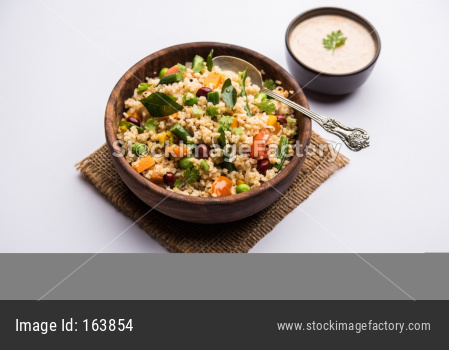 Broken wheat or Daliya Upma, served in a bowl. selective focus