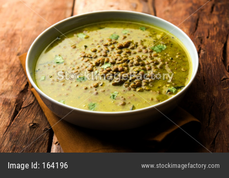 Black Masoor Dal fry or Dhaba Style Sabut Red Lentil dhal tadka in green curry, served in a bowl. selective focus