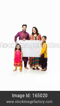 Indian family celebrating Diwali while holding blank white board / placard. Standing isolated over white background and looking