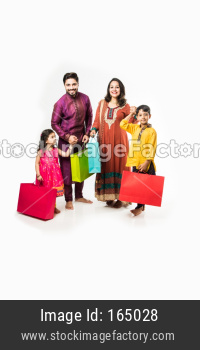 Indian family celebrating Diwali / Deepavali in traditional wear with shopping bags, standing isolated over white background