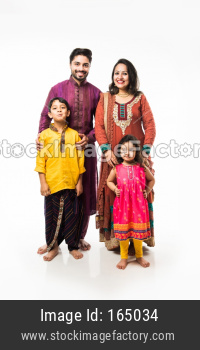 Indian young family of four in traditional wear, standing isolated over white background