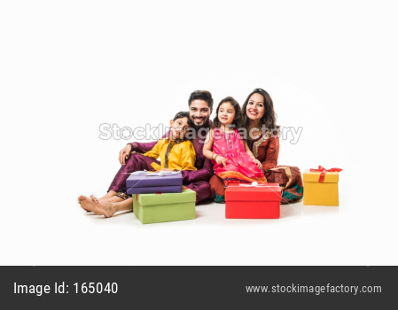 Indian family celebrating Diwali / Deepavali in traditional wear while sitting isolated over white background with gift boxes an