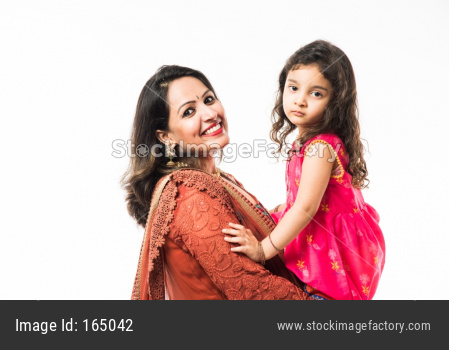 Portrait of Happy Indian mother hugging her daughter in traditional ethnic clothes on some festival day, standing isolated over