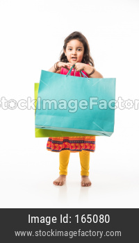 Indian small girl holding shopping bags, standing isolated over white background