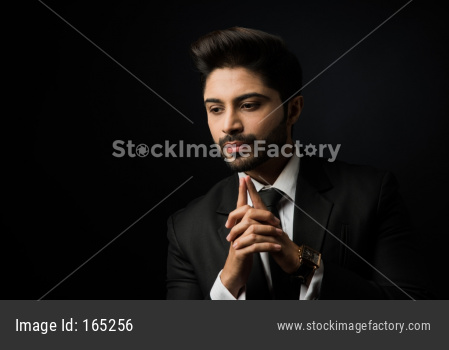 Portrait of Indian Male businessman standing against black background