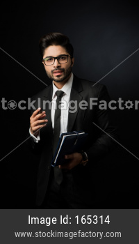 Indian Male businessman writing in a diary while standing against black background, moody lighting, selective focus