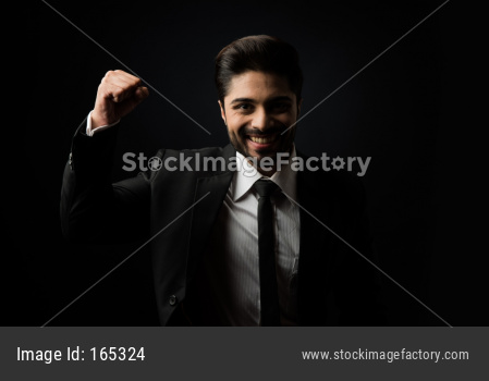 Indian Bearded Male businessman celebrating success with thumbs up or raising fist while standing isolated over white background