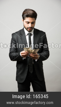 Happy bearded Indian businessman holding fan in hand, Indian Rupee currency bills of 500 , standing isolated over white backgrou