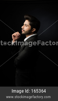 Indian bearded Male businessman showing side profile, standing over black background