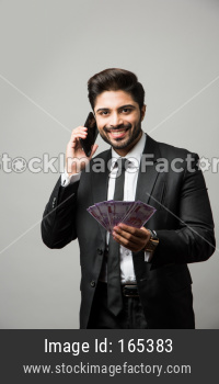 Indian businessman pointing at you, standing isolated over white background