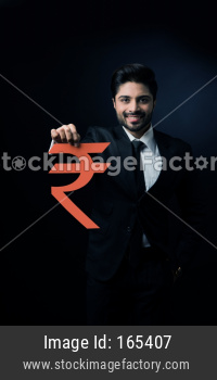 Indian businessman holding rupee sign made out of paper