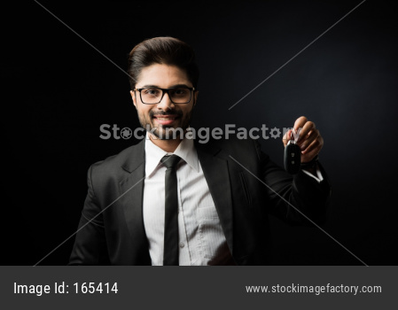 Indian businessman with Car Keys, standing isolated over black background