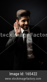 gossip / Rumour - Indian Businessman listening with eavesdropping pose over black background