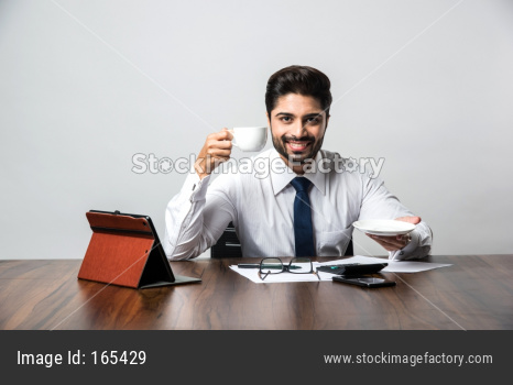 Indian businessman having coffee / tea at work / office, sitting at desk or table holding cup and saucer