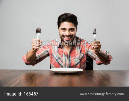 empty plate and Indian man with beard holding spoon and fork, wearing checkered shirt and sitting at table