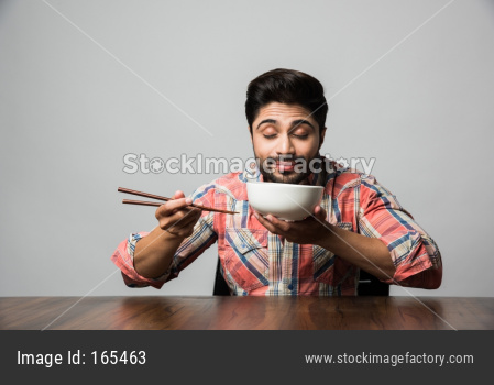 empty bowl and Indian man with beard holding spoon or chopsticks, wearing checkered shirt and sitting at table