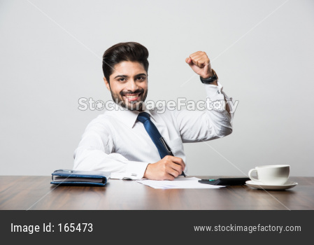 Indian Bearded Male businessman celebrating success with thumbs up or raising fist while sitting at table / desk in office