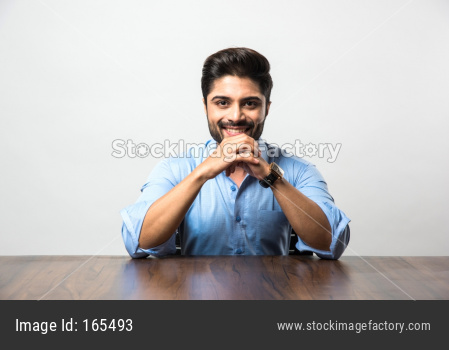 Portrait of Indian Male businessman sitting at table / desk in office, over grey background