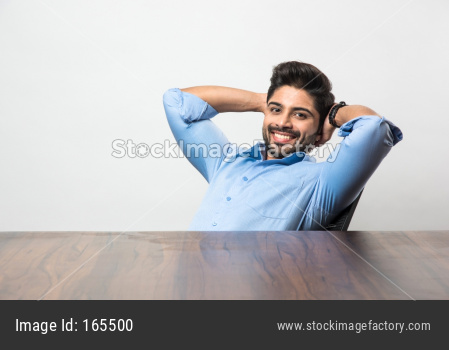 Indian businessman relaxing / stretching  at workstation in office