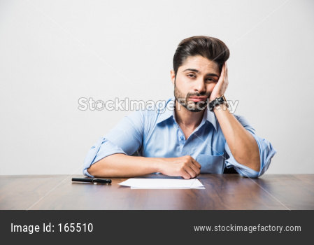Stressed Indian Businessman having headache or Migraine pain while working at office table