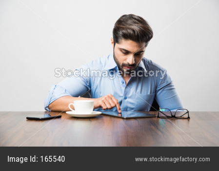 Indian business man using cell phone. Having Conversation or typing or checking social media feeds