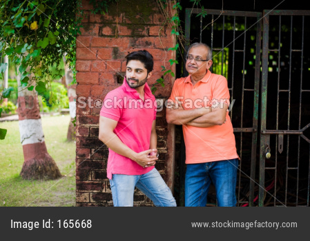Young Man with Father posing against red brick wall, outdoor