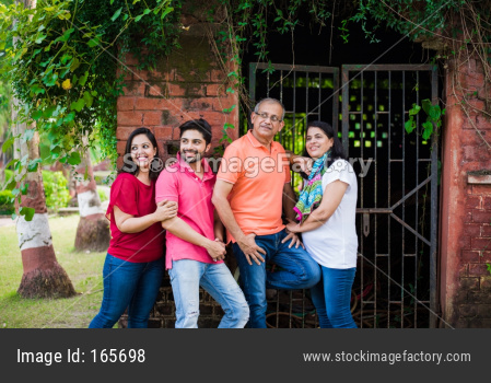 young and senior indian family of 4 standing against brick wall outdoor