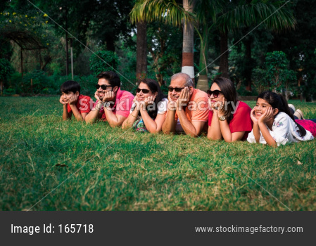 indian family lying on grass with hands on chin