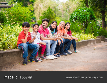indian family of 6 sitting at wall in garden / park