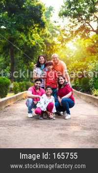 indian family of 6 posing on walkway for photograph
