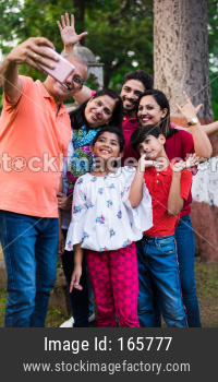 indian grandfather taking selfie picture of his family includes his wife, son, daughter in law and grand children