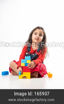 Indian Little child girl with stethoscope and Stuffed Baby or Puppy toy sitting against white background