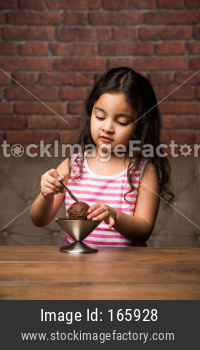Indian Small girl eating Ice Cream in a bowl