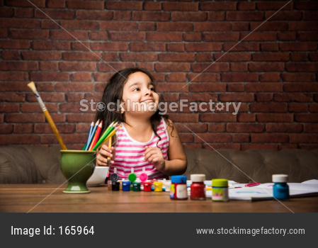 Indian small girl drawing / Painting with colours over paper, selective focus