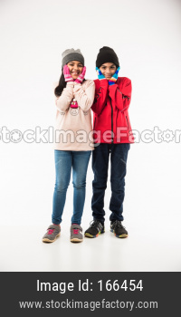Indian boy and girl in warm cloths standing against white background