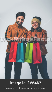 Indian family with shopping bags in winter wear /warm clothes against background