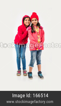 Two Indian cute little girls in winter wear, standing against white background