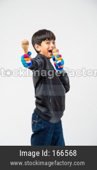 Indian kid / boy eating ice cream in warm clothes on white background
