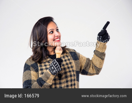 Indian girl / female eating ice cream while wearing warm winter clothes on white background