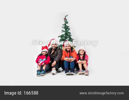 Indian family celebrating Christmas in warm clothes with tree in the white background