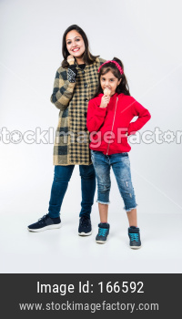 Indian father and daughter eating ice cream in cone while wearing warm clothes on white background