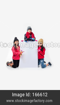 Indian kids in warm clothes holding white board, Indian winter fashion