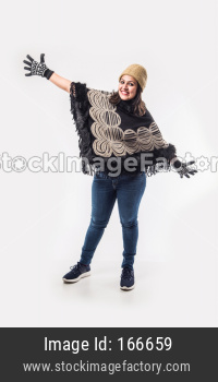 Indian Lady / woman in winter wear presenting or with hands stretched, standing isolated over white background
